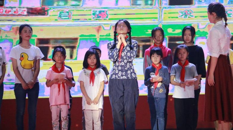 """我校学生在舞台合唱歌曲""""虫儿飞"""",演绎留守儿童对生活的期待,表现留守"""